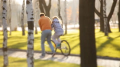 Young and joyful couple learning to ride a bicycle and airship on it in the park Stock Footage