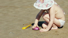 Cute child plays on the beach sand by the sea. Stock Footage