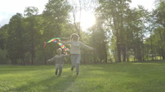 Mother and child running flies with them kite in the park sunlight. Slow motion Stock Footage