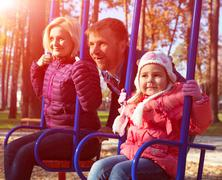Young Jolly Family Having Fun on Kids Seesaw in Park - stock photo