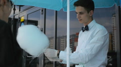 Young guy making cotton candy on a special machine, it wears bow tie, behind him Stock Footage
