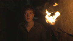 Torch man walking exploring dark cave with fire lit burning torch Urban Explo Stock Footage