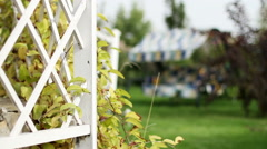 View of the exterior of a contemporary garden. Wooden fence and garden swing - stock footage