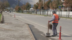 Antalya, Turkey - March 2016: the janitor sweeping the roadside roadway Stock Footage