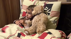 Adorable toddle in bed with his Teddy bear Stock Footage