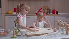 Two little blonde sisters in aprons standing together in the kitchen and playing Stock Footage