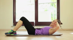 Woman doing abdominal crunches exercise and looks in the laptop on the floor  HD Stock Footage