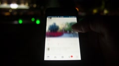 Facebook browsing on iphone touchscreen smartphone at night - stock footage