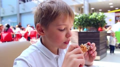 The child eats a chicken in a fast food Stock Footage