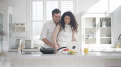 4K Couple dancing in the kitchen at home, listening to music on laptop Stock Footage