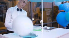 Young guy making cotton candy on a special machine, it wears bow tie, behind him - stock footage