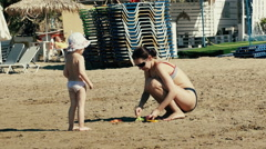 Funny little girl and mother playing by the sea. - stock footage