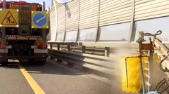 city road cleaning machine clearing road barriers with water jet - stock footage