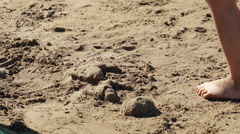Child and mother playng on the beah sand by the sea. Stock Footage