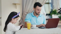 A man working on a laptop with him 6 years old girl using a mobile phone Stock Footage