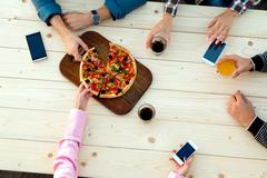 Hands of People at Wood Cafe Pizza Table with Drinks Food and Electronic Gadgets - stock photo