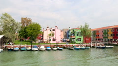 Domestic passenger boat is passing colorful houses in Burano island Stock Footage