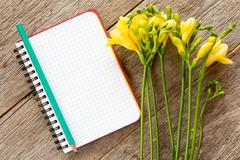 Yellow freesia flowers and blank notebook Stock Photos