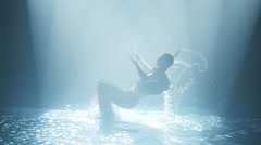 Dancer does a somersault in the water in a circle of light Stock Footage