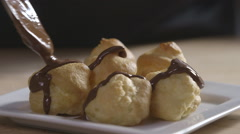 Chocolate sauce dribbled over profiteroles - stock footage