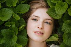 Attractive tender young woman surrounded by green leaves Stock Photos