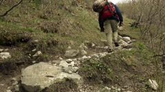 Hiker with red backpack walking uphill 4K video Stock Footage