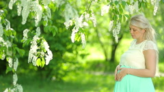 Portrait of a pregnant woman with long blond hair in the garden. Stock Footage