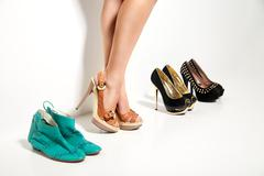 Woman's legs and many shoes over white - stock photo