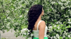 Young beautiful brunette woman in blooming garden - stock footage