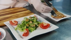 Chef preparing salad Caesar, in the frame only hands visible Stock Footage