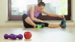 Weight loss concept with apple, dumbbells and stretching woman HD Stock Footage