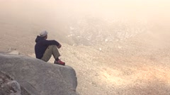 Young man sitting on rock and sightseeing beautiful hazy mountains. 4k shot Stock Footage