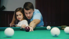 Dad teaches his daughter to play billiards. It shows how to hold the cue - stock footage