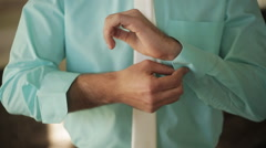 Groom buttoning the cuffs of his shirt color Tiffany Stock Footage
