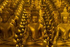 Golden Buddha Statues Lined Up Inside Buddhist Temple in Thailand - stock photo