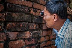 Old Archaeologist using magnifying  lens watching on ancient old brick wall i Stock Photos