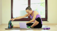 Young pretty woman sitting in front of laptop and stretching her legs HD Stock Footage