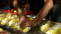 Fresh sliced fruits stand on food market, street food scene, handheld shot Stock Footage
