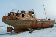 Old rusty ship on winter shore of Lake Baikal - stock photo