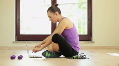 Sporty smiling woman using laptop in bright room HD Stock Footage
