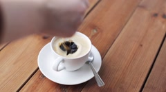 Hand dropping sugar into coffee cup on table Stock Footage