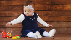 Little baby girl playing with plush toys - stock footage