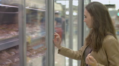 Young woman standing next to shelf with meat in the refrigerator Stock Footage