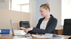 Office worker smiling and working on a laptop. Stock Footage