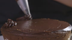 Piping ganache onto a chocolate cake - stock footage