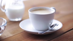 Coffee cup and beans pouring to wooden table Stock Footage