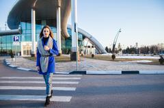 Side view of brunette in blue coat going on crosswalk Stock Photos