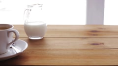 Sugar falling to coffee cup on wooden table Stock Footage