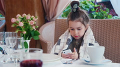 Girl 6 years of using a mobile phone in a cafe. It is wrapped in a blanket, she Stock Footage