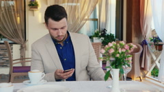 Serious and puzzled man reading sms on the phone. Sitting in a cafe on a summer Stock Footage